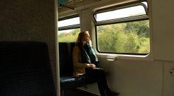 Nachdenkliche junge Frau im Zug unterwegs — Stockfoto
