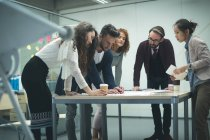 Business executives discussing over blueprint in office — Stock Photo