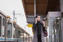 Femme en hijab parler téléphone mobile à la gare — Photo de stock
