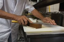 Seniorchef hält Messer in Hotelküche — Stockfoto