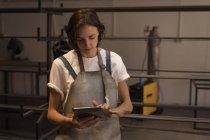 Young female welder using digital tablet in workshop. — Stock Photo
