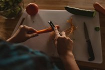 High angle view of girl standing in kitchen and peeling carrot with peeler. — Stock Photo