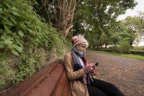 Mujer joven sentada en el banco usando su teléfono móvil en el parque - foto de stock