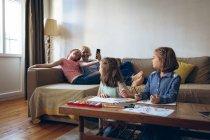 Дети взаимодействуют с матерью в гостиной на дому — стоковое фото