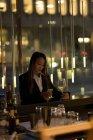 Femme debout au bar des champagne tout en utilisant son téléphone dans l'hôtel — Photo de stock