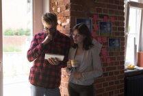 Мужские и женские руководителей обсуждения над цифровой планшет в офисе — стоковое фото