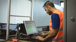 Masculino trabalhador trabalhando no computador da fábrica — Fotografia de Stock