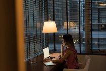 Бизнесмен, сидящая на стуле и работающая над ноутбуком в офисе — стоковое фото