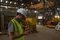 Engenheiro naval usando telefone celular na oficina — Fotografia de Stock