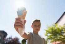 Garçon tenant double scooped crème glacée par une journée ensoleillée — Photo de stock