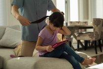 Дівчина, використовуючи цифровий планшет, а батько розчісувати волосся в домашніх умовах — стокове фото