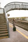 Woman waiting for the train with luggage at railway platform — Stock Photo