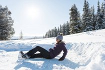 Woman falling while skating in snowy landscape during winter. — Stock Photo