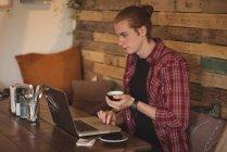 Mann benutzt Laptop beim Kaffeetrinken im Café — Stockfoto