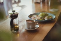 Breakfast and coffee on wooden table in cafe — Stock Photo