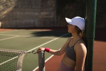 Jeune femme appuyé sur un poteau dans le court de tennis — Photo de stock