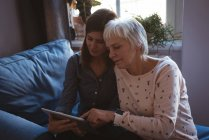 Senior woman and daughter using a tab while siting on the sofa during day time — Stock Photo