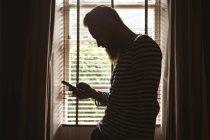 Человек, стоящий у окна, используя свой мобильный телефон дома — стоковое фото
