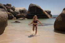 Ragazza che corre in mare alla spiaggia in una giornata di sole — Foto stock