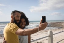 Romantic couple taking selfie with mobile phone near beach on a sunny day — Stock Photo