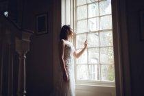 Verträumte Braut schaut zu Hause aus dem Fenster — Stockfoto