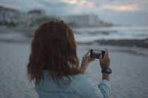 Rear view of woman taking photo with mobile phone at beach — Stock Photo