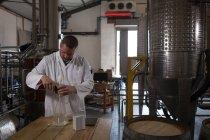 Чоловічий працівник перевірки якості Джин заводі — Stock Photo