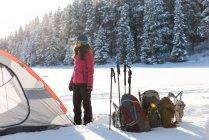 Mujer de pie junto a la tienda en paisaje nevado durante el invierno - foto de stock