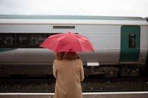 Vista traseira da mulher jovem e bonita com guarda-chuva, esperando o trem na plataforma — Fotografia de Stock