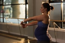 Pregnant woman doing stretching exercise at home — Stock Photo