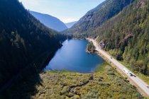 Высокий угол обзора озера и дороги среди покрытых лесом гор — стоковое фото