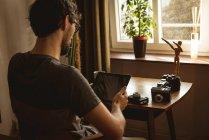 Людина, використовуючи цифровий планшетний у вітальні на дому — стокове фото