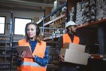 Женщина-работница ведет учет цифровых планшетов на фабричном складе — стоковое фото