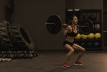 Fit woman exercising with barbell in the studio — Stock Photo