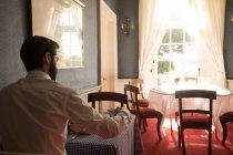 Vue arrière du marié prenant le thé à table — Photo de stock