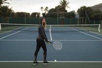 Joven mujer sosteniendo bola de raqueta y pista de tenis en cancha de tenis - foto de stock