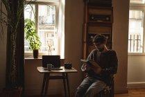 Uomo lettura libro in soggiorno a casa — Foto stock
