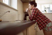 Femme buvant du café dans la cuisine à la maison, vue à angle bas . — Photo de stock