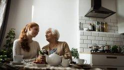 Бабушка и внучка смотрят друг на друга в гостиной дома — стоковое фото
