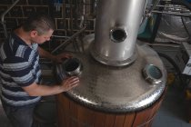 Чоловічий працівник перевірки машини лікеро-горілчаний завод в заводу — Stock Photo