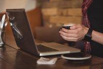 Seção média do homem usando laptop enquanto toma café no café — Fotografia de Stock