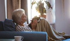 Старшая женщина отдыхает на диване, гладит кошку в гостиной дома — стоковое фото