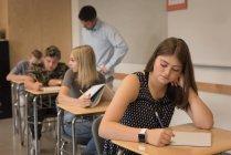 Thoughtful teenage girl sitting in classroom at university — Stock Photo
