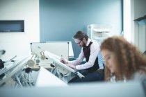 Мужчина-руководитель, работающий над чертежным столом в офисе — стоковое фото