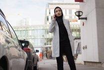 Mulher no hijab falando no telefone celular na rua da cidade — Fotografia de Stock