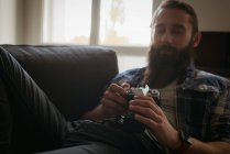 Man reviewing picture on digital camera while relaxing on sofa — Stock Photo