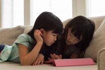 Hermanos usando tableta digital en la sala de estar en casa - foto de stock