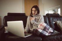Donna che prende il caffè mentre usa il computer portatile in soggiorno a casa . — Foto stock