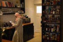 Mulher muçulmana olhando para a impressão na cozinha em casa — Fotografia de Stock