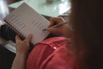 Schwangere schreibt zu Hause in Notizbuch — Stockfoto